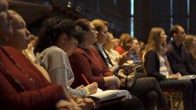 RUSIA, MOSCÚ - 13 DE ABRIL DE 2019: La audiencia de las mujeres que escucha los entrenamientos y las conferencias de la informaci fotografía de archivo libre de regalías