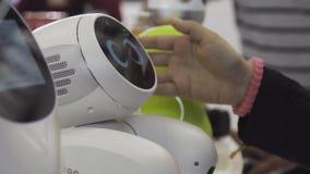 Rusia, Moscú - 25 de agosto de 2018: Gente que juega con el robot del humanoid durante la exposición internacional de la tecnolog almacen de video
