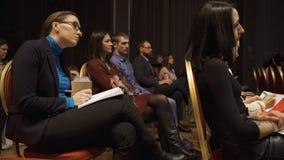 RUSIA, MOSC? - 13 DE ABRIL DE 2019: La audiencia de las mujeres que escucha los entrenamientos y las conferencias de la informaci fotografía de archivo