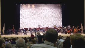 Rusia, Novosibirsk, 12 puede 2017 Los espectadores se sientan delante del funcionamiento en etapa, la orquesta sinfónica metrajes
