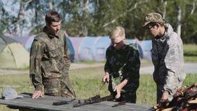 Rusia, Novosibirsk, 2018 Rifle de asalto del Kalashnikov de AK-47 del estudio del recluta de tres cadetes almacen de video