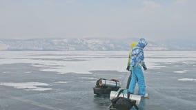 Rusia, Olkhon - 28 de febrero de 2018: Grupo de turistas con los trineos del hielo que caminan a lo largo del hielo del lago Baik almacen de video