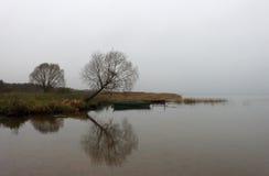 Rusia, Pereslavl-Zalessky, lago Pleshcheevo Árboles y barcos secos con la reflexión en el lago en el día cubierto, visión horizon Imagenes de archivo