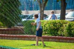 Rusia, Rostov-On-Don 16 de agosto de 2018 un muchacho del adolescente juega con un espray del agua de un sistema de irrigación Fotografía de archivo
