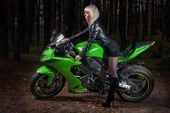 RUSIA Ryazan, 20 10 2016 - muchacha hermosa joven en una motocicleta portuaria Kawasaki zx-10r en el camino oscuro foto de archivo libre de regalías