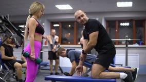 Rusia, Samara - 13 de noviembre de 2018: el instructor muestra a cliente cómo hacer ejercicio en el gimnasio metrajes