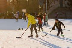 Rusia, Saratov, el 13 de enero de 2018, mide el tiempo de 15 00 Gente que patina en la pista de hielo y que juega a hockey en el  Imagen de archivo libre de regalías
