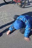 Rusia, Severomorsk - 1 de mayo de 2018: Las pinturas del muchacho en el asfalto fotografía de archivo libre de regalías