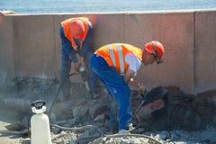 Rusia St Petersburg julio de 2016 dos trabajadores que reparan el terraplén Imagen de archivo