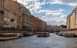 RUSIA, ST PETERSBURG 2014: Turistas afortunados del barco de placer a lo largo del río de Moika en fondo de la arquitectura histó Fotos de archivo libres de regalías