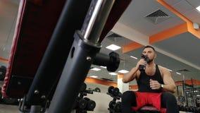 Rusia, Togliatty - 23 de febrero de 2019: Agua potable del hombre adulto en el gimnasio El individuo utiliza una sacudida de la p almacen de metraje de vídeo