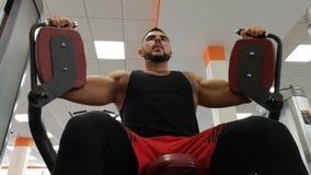 Rusia, Togliatty - 23 de febrero de 2019: El hombre atlético entrena a los músculos pectorales en el gimnasio, haciendo aptitud almacen de video