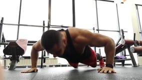 Rusia, Togliatty - 23 de febrero de 2019: El hombre joven de los deportes realiza flexiones de brazos en el gimnasio Contratan al metrajes