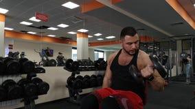 Rusia, Togliatty - 23 de febrero de 2019: Hombre de la pesa de gimnasia en el levantamiento de pesas de la aptitud del bíceps del almacen de metraje de vídeo