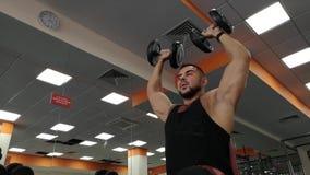 Rusia, Togliatty - 23 de febrero de 2019: Hombre de la pesa de gimnasia en el levantamiento de pesas de la aptitud de las manos d metrajes