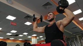Rusia, Togliatty - 23 de febrero de 2019: Hombre de la pesa de gimnasia en el levantamiento de pesas de la aptitud de las manos d almacen de metraje de vídeo
