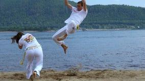 Rusia, Togliatty - 11 de julio de 2018: El hombre y la mujer entrenan al capoeira en la playa - concepto sobre gente metrajes