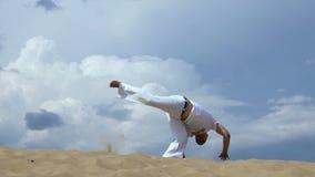 Rusia, Togliatty - 11 de julio de 2018: El individuo joven entrena a capoeira en backround del cielo golpee adentro el salto con  almacen de video