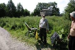 Rusia - Usolye el 16 de julio de 2017: viejo pintor con las pinturas del cepillo a disposición en lona en naturaleza Fotografía de archivo