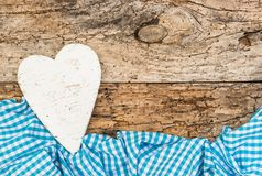 Rusitc white wooden heart with blue checked fabric on old wood with copy space. White wooden heart with blue textile frame on old wood background with copy space Royalty Free Stock Photos