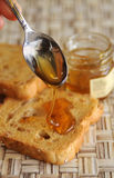 Rusk bread with honey. Spoon pouring honey over rusk bread Stock Images