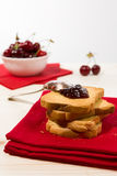 Rusk with cherry jam over a red napkin Stock Photography
