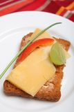 Rusk with dutch cheese. A rusk or melba toast canape with dutch cheese, half a grape, a sliver of capsicum and a chive, on a white plate Stock Photos