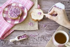 Flat lay with rusk, sweet pink purple sprinkles and cup of tea. Against wooden background stock photos