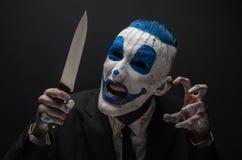 Ruskig clown och allhelgonaaftontema: Galen blåttclown i en svart dräkt med en kniv i hans hand som isoleras på en mörk bakgrund  Royaltyfri Fotografi