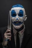 Ruskig clown och allhelgonaaftontema: Galen blåttclown i en svart dräkt med en kniv i hans hand som isoleras på en mörk bakgrund  Arkivbild