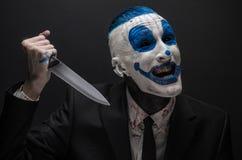 Ruskig clown och allhelgonaaftontema: Galen blåttclown i en svart dräkt med en kniv i hans hand som isoleras på en mörk bakgrund  Royaltyfri Bild