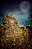 Ruskig kyrkogård för allhelgonaafton med gamla gravstenkors, månen och en flock av galanden Royaltyfri Fotografi
