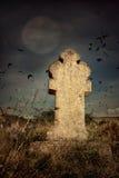 Ruskig kyrkogård för allhelgonaafton med gamla gravstenkors, månen och en flock av galanden Royaltyfria Foton