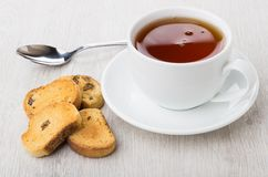 Rusks with raisin, tea in cup with saucer and teaspoon. On wooden table Stock Photography