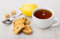 Rusks with raisin, tea, lemon, lumpy sugar and teaspoon. On wooden table Royalty Free Stock Photos