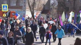 Rusland Berezniki kan 1, 2018: een kolom van mensen met ballen en de vlaggen gaan langs het vierkant stock videobeelden
