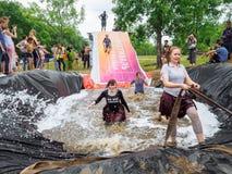 RUSLAND, Bryansk - Juni 30, 2018: Hindernisras Atleten in kostuumssprong in een kuil van water stock foto