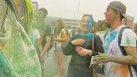 RUSLAND, IRKOETSK - JUNI 27, 2018: Gelukkige jongeren die en tijdens Holi-Festival van Kleuren dansen vieren Menigte van