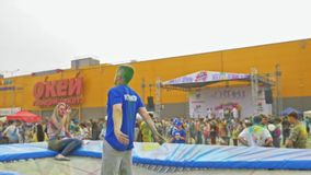 RUSLAND, IRKOETSK - JUNI 27, 2018: Gelukkige jongeren die en tijdens Holi-Festival van Kleuren dansen vieren Menigte van stock footage
