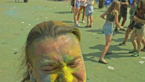 RUSLAND, IRKOETSK - JUNI 27, 2018: Gelukkige jongeren die en tijdens Holi-Festival van Kleuren dansen vieren Menigte van stock video