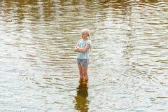 Rusland Karelië Kondopoga - 08-2014 Juli: een meisje bevindt zich in een fontein in een vulklei van water en doorweekte ernstig royalty-vrije stock fotografie