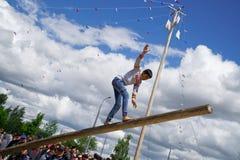 Rusland, Magnitogorsk, - 15 Juni, 2019 De jongen brengt op een logboek in evenwicht tijdens Sabantuy - de nationale feestdag van  royalty-vrije stock fotografie