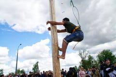 Rusland, Magnitogorsk, - 15 Juni, 2019 Een mens beklimt een gift op een hoge houten pool tijdens Sabantuy - de nationale feestdag stock foto