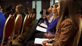 RUSLAND, MOSKOU - APRIL 13, 2019: De vrouwen zitten bij de bedrijfs opleiding met notitieboekjes Art De mooie dames zitten en lui stock afbeelding