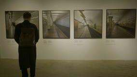 RUSLAND, MOSKOU - 10 JUNI 2017: Mens die in galerijruimte beeldenkaders bekijken Zakenman in kunstgalerie het kijken Royalty-vrije Stock Afbeeldingen