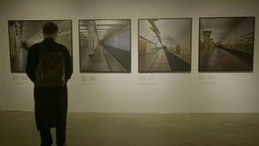 RUSLAND, MOSKOU - 10 JUNI 2017: Mens die in galerijruimte beeldenkaders bekijken Zakenman in kunstgalerie het kijken Stock Foto's
