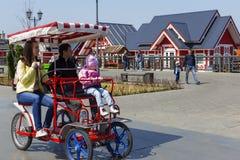 Rusland, Moskou, kan 3, 2018, familie in het Park die een rolstoel berijden, redactie stock fotografie