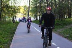 Rusland, Moskou, kan 12, van 2018, van de vader en van de dochter berijdende fietsen in het Park, redactie royalty-vrije stock foto's