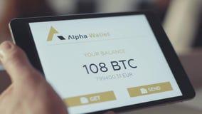 Rusland, Moskou - Mei 2018: de mens controleert de rekening op de tablet voorraad Het controleren van het bitcoinsaldo op de reke stock video