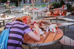 Rusland Moskou - 14 SEPTEMBER, eenzame de mens van 2012 A zit dichtbij vuile lijsten met huisvuil dichtbij het snelle voedsel van Stock Afbeeldingen